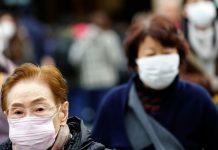 一名从中国回日本的男子经测试呈阳性后,东京的行人戴着防护口罩。