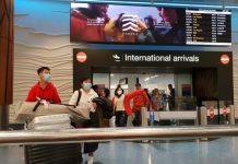 从广州和上海出发的航班已经降落在奥克兰机场,中国乘客戴着口罩过关。