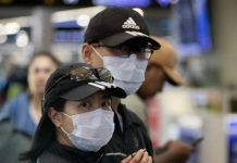戴着口罩的旅行者离开奥克兰国际机场的到达大厅。