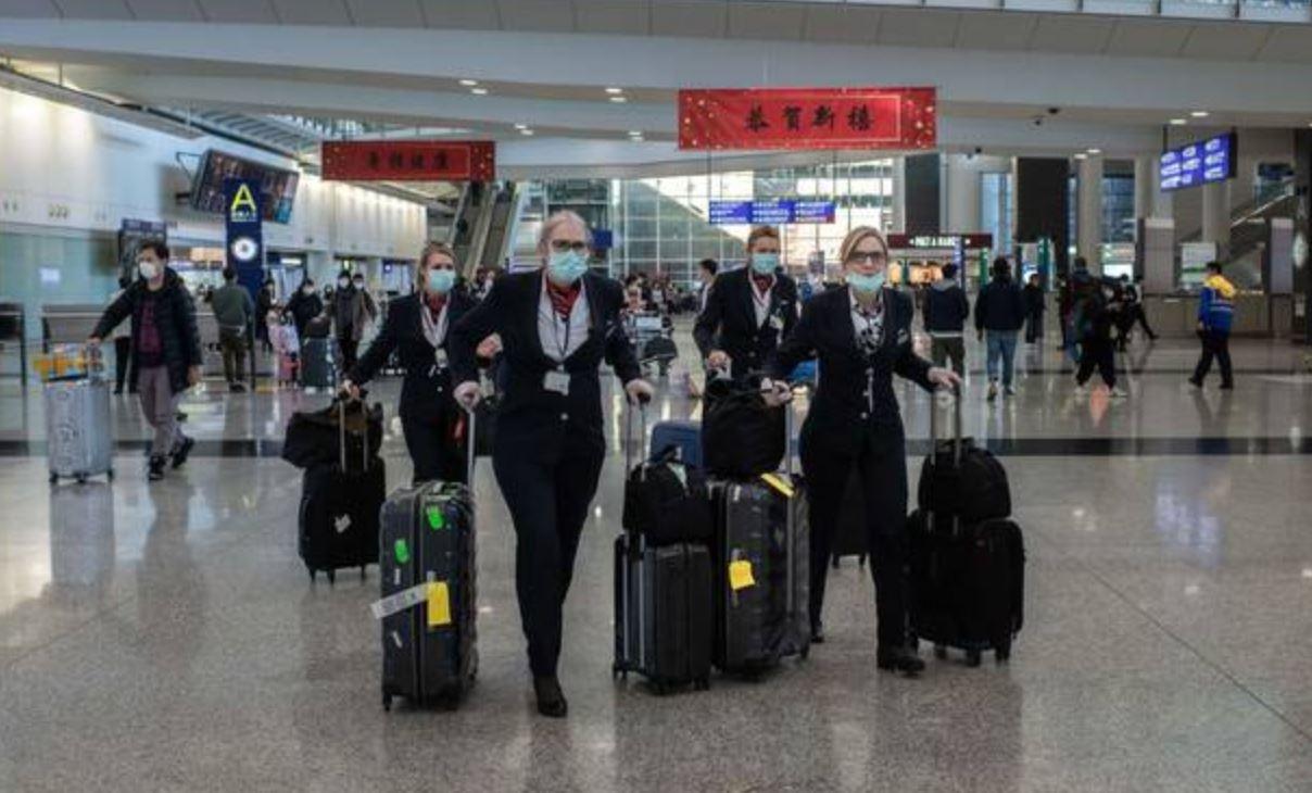 2020年1月30日,星期四,飞行机组人员在中国香港国际机场的到达终点大厅戴着口罩。