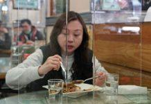 香港一名食客午餐时在桌上摆了透明塑料面板,以防冠状病毒传播。